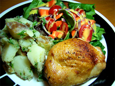 Baked chicken thigh, potato salad, and garden salad.