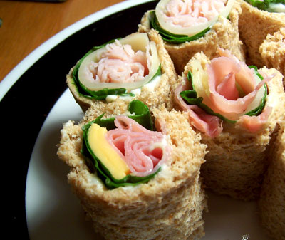 Sandwich Sushi with Whole Wheat Bread, Mayo, Dijon Mustard, American and 2% Swiss Cheese, Spinach, and Deli Ham and Turkey